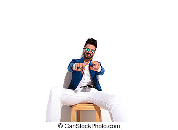 serious fashion man sitting and pointing with both hands