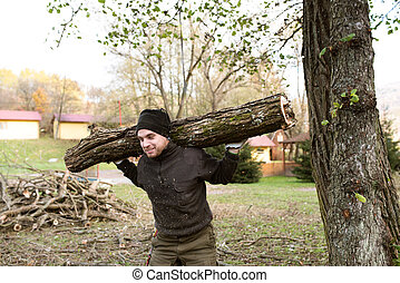 Man carrying tree trunk on his shoulders for heating in...