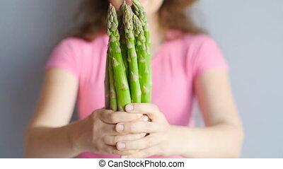 Fresh green asparagus in a woman's hands - Fresh green...