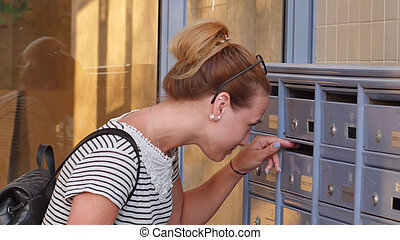 Pretty young woman checking her mailbox for new letters....