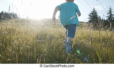 Boy Running Through Wet Grass - Happy kid boy wears colored...