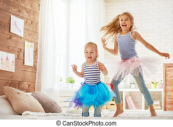 sisters jumping on the bed - two cute children baby girls...