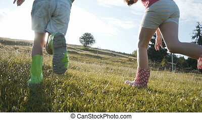 Kids Running on Wet Grass - Two happy kid girls wears...