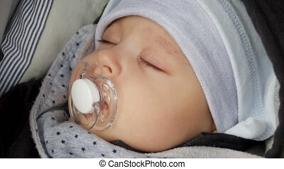 baby boy in hat four months with a pacifier sleeps