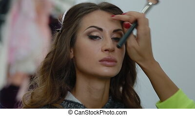 Makeup artist doing visage to beautiful girl