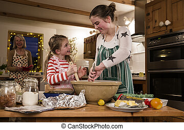 Baking With Grandma - Two sisters are baking cakes in the...