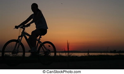 Young Woman Riding Bicycle Sunset Backlit Silhouette -...