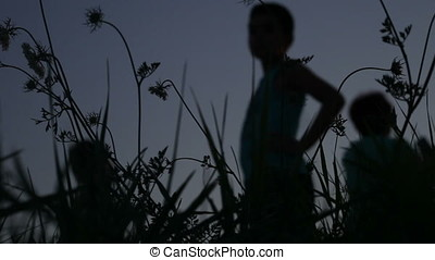Children Watching Running Away Silhouettes At Sunset Against Twilight Sky