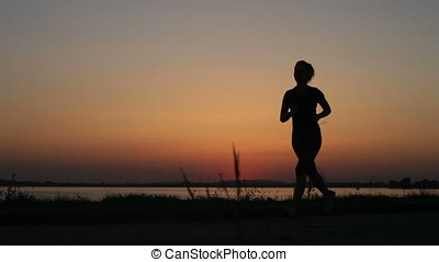 Young Woman Old Man Jogging On Lake Shore Sunset Backlit Silhouettes