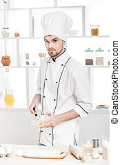 Chef in uniforms whipping eggs and milk in bowl in kitchen -...