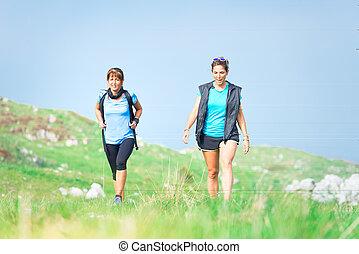 Due donne amiche praticano trekking in montagna.