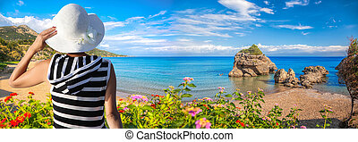 Woman holding a hat against Porto Zorro beach on Zakynthos...