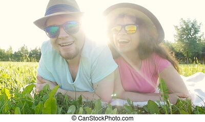 Young couple lying down in grass and smiling - Happy young...