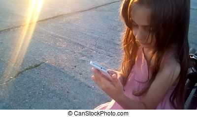 Little Girl Playing Mobile Phone Games Sunset Back Light -...