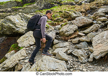 Young hiker with backpack on a trail - Young man with...