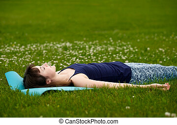 Girl doing yoga, meditating, Shavasana or corpse position in...