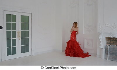 Gergeous woman in red dress posing in studio.