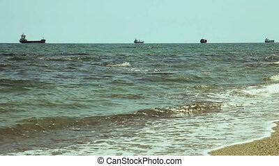 Cargo ships at horizon line in open ocean