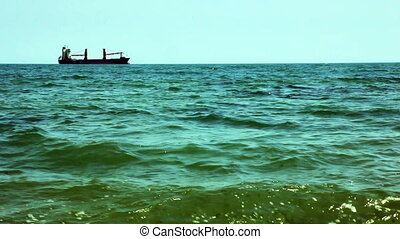 Large cargo ship at horizon line in open ocean