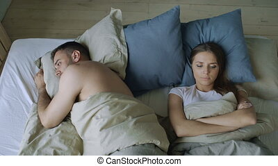 Top view of upset lying sleepless couple in bed offended...