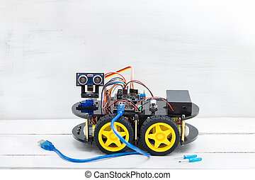 robot on four wheels and a variety of cables with big blue wire
