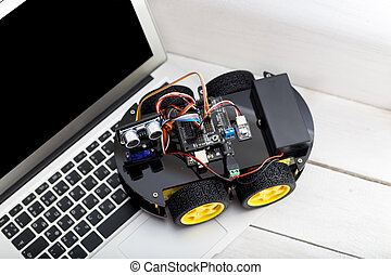 robot on four wheels with a laptop on a wooden white table