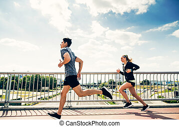 Young couple in the city running on a bridge.
