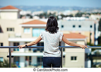 Woman enjoying cityscape standing on rooftop