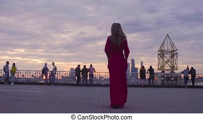 Young woman in red dress is walking on a square - Gold time...