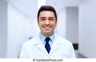 smiling doctor in white coat at hospital - healthcare,...