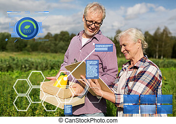 senior couple with box of vegetables at farm - organic...