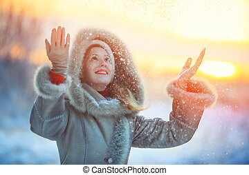 Woman throwing up snow - Young happy woman in warm winter...