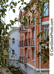 The facade of brick houses with wrought-iron balconies on...