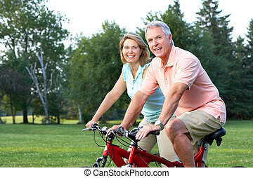 seniors couple biking - Happy elderly seniors couple biking...