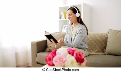happy woman with tablet pc and headphones at home - people,...