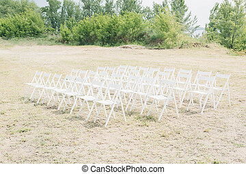 Many rows of white wooden chairs for wedding ceremony in...