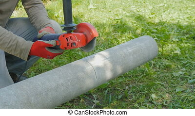 The worker cuts the pipe from asbestos, into two parts. - A...