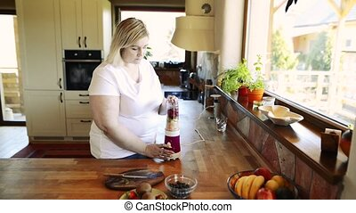 Unrecognizable overweight woman preparing healthy smoothie....