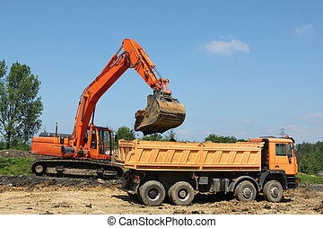 Road construction - Excavator feeding the dump truck. Road...