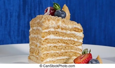 Layer cake with cuted strawberry and blueberries on plate....