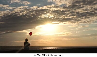 Lonely woman with heart balloon watching sunset - Back view...