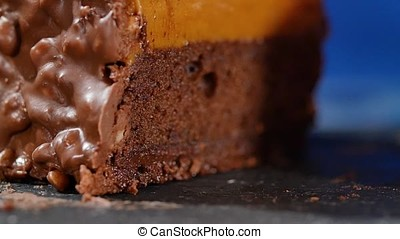 Cake with cream and nuts. Chocolate cake with nuts and chocolate chips. Chocolate caramel cupcake with nuts and butterscotch syrup, close up