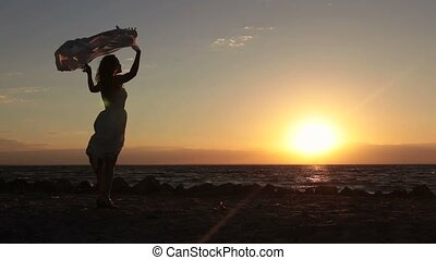 Joyful woman with flying scarf on beach at sunset