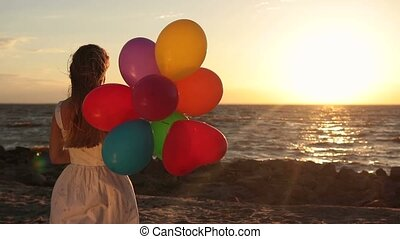 Girl with colorful balloons on beach at sunset