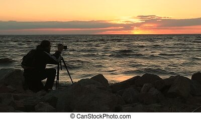 Photographer taking photos of seascape at sunset - Young...