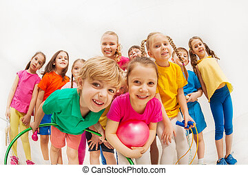 Sporty kids and gymnastics coach having fun in gym -...