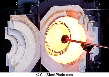 Spinning Molten Glass in Oven - A glass blower spinning...