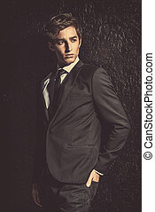 black suit male - Portrait of a handsome young man posing in...
