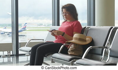 Young woman at international airport looking at smartphone...