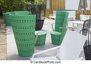 Restaurant with green wicker chairs, tables and different colors of chairs